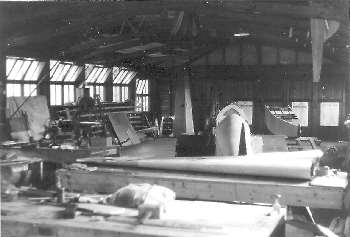 In the workshop, rear view of G-AFSV under construction with the fifth uncompleted  Carden fuselage to its right.